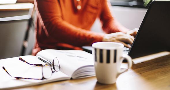 Persona escribiendo, taza de café, libro y anteojos