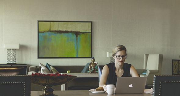 Mujer trabajando desde casa en computadora portatil